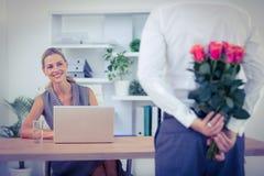 Bouquet de dissimulation d'homme devant la femme d'affaires au bureau Images stock