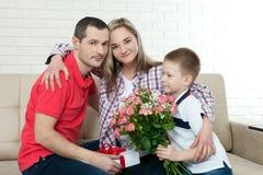 Bouquet de dissimulation de fils pour étonner la maman le jour du ` s de mère femme, homme Photographie stock libre de droits