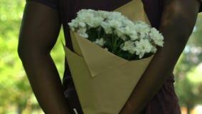 Bouquet de dissimulation masculin d'afro-américain des fleurs blanches derrière son dos, surprise clips vidéos