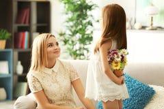 Bouquet de dissimulation de petite fille des fleurs pour son dos de mère derrière Image libre de droits