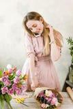 Bouquet de fête et entretien de paquet de fleuriste au téléphone Photographie stock libre de droits