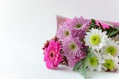 Bouquet de fleur dans une enveloppe rose sur l'espace blanc de copie de fond images stock