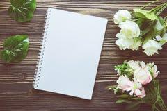Bouquet de fleur et de carnet vide de journal intime sur la table en bois rustique avec l'espace de copie Photographie stock