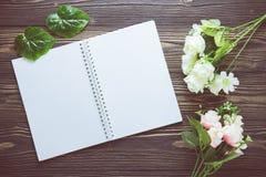 Bouquet de fleur et de carnet vide de journal intime sur la table en bois rustique avec l'espace de copie, calibre de maquette Photos stock