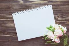 Bouquet de fleur et de carnet vide de journal intime sur la table en bois rustique avec l'espace de copie, le calibre de maquette Photo libre de droits