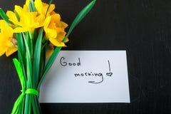 Bouquet de jonquille près de carte avec bonjour sur le fond noir Vue supérieure Copiez l'espace Jour de mères ou jour des femmes  Image stock