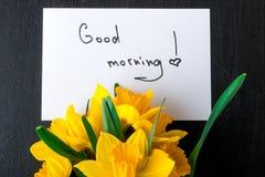 Bouquet de jonquille près de carte avec bonjour sur le fond noir Vue supérieure Copiez l'espace Jour de mères ou jour des femmes  Images libres de droits