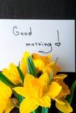 Bouquet de jonquille près de carte avec bonjour sur le fond noir Vue supérieure Copiez l'espace Jour de mères ou jour des femmes  Photographie stock libre de droits