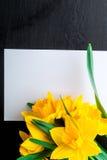 Bouquet de jonquille près de carte vide sur le fond noir Vue supérieure Copiez l'espace Jour de mères ou jour des femmes salutati Image stock