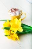 Bouquet de jonquille près de tasse de café sur le fond en bois blanc Fin vers le haut Photographie stock