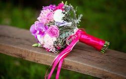 Bouquet de la fleur de la jeune mariée se trouvant sur un puits en bois Image libre de droits