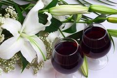 Bouquet de lis et deux glaces de vin rouge image libre de droits