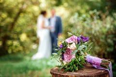 Bouquet de mariage avec le ruban pourpre sur une surface en bois Image libre de droits