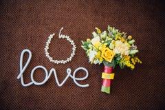 Bouquet de mariage avec les bijoux nuptiales sur un tapis brun Images stock