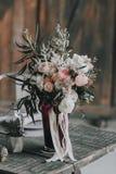 Bouquet de mariage avec les roses blanches et roses et d'autres fleurs sur une table rustique dessin-modèle indoors Images stock