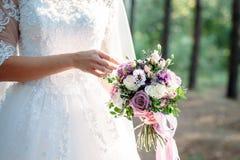 Bouquet de mariage dans des mains du ` s de jeune mariée photographie stock