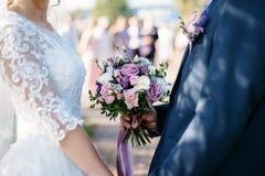 Bouquet de mariage dans des mains du ` s de jeune mariée images stock