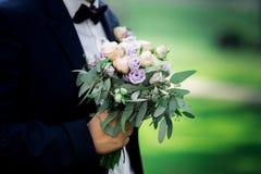 Bouquet de mariage dans les mains du marié Image libre de droits