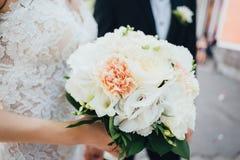 Bouquet de mariage dans les mains du ` s de jeune mariée Photographie stock libre de droits