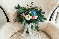 Bouquet de mariage des fleurs fraîches pour la jeune mariée se tenant sur le fauteuil Photos libres de droits