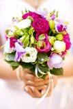 Bouquet de mariage des roses blanches et des orchidées roses dans des mains de jeune mariée Images stock