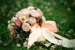 Bouquet de mariage des roses roses et blanches se trouvant sur l'herbe Photo libre de droits