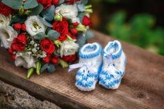 Bouquet de mariage des roses et des butins de bébé sur le fond en bois Photos libres de droits