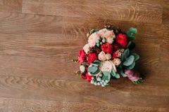 Bouquet de mariage du rouge et des roses de crème sur un plancher en bois Vue supérieure Image stock