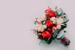 Bouquet de mariage du rouge et des roses de crème sur un plancher léger Vue supérieure Images stock