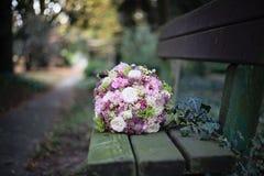 Bouquet de mariage sur le banc en parc Images stock
