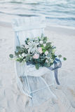 Bouquet de mariage sur une chaise au bord de la mer Photographie stock libre de droits