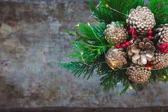 Bouquet de Noël avec les cônes d'or de pin, les baies rouges et l'arbre sur le fond en bois photos stock