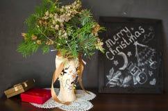 Bouquet de Noël sur la table en bois avec le rouge et le boîte-cadeau d'or Image libre de droits