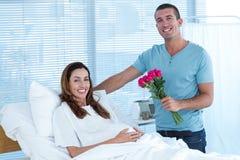 Bouquet de offre d'homme bel des fleurs à son épouse enceinte Photo libre de droits