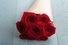 Bouquet de papier rustique de sept roses rouges sur la table en bois bleue Image stock