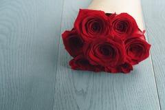 Bouquet de papier rustique de sept roses rouges sur la table en bois bleue Photo stock