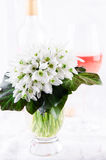 Bouquet de perce-neige, fleurs blanches de ressort et vin rose sur le fond clair Copiez l'espace Images stock