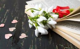 Bouquet de perce-neige sur le livre ouvert avec des coeurs Photo stock
