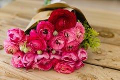 Bouquet de ranunculus rose enveloppé dans le mensonge de papier de métier sur le rusti Photo stock