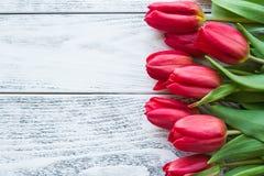 Bouquet de ressort des tulipes rouges sur la vue supérieure en bois de table Images stock