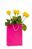 Bouquet de roses jaunes dans un sac de papier rose, d'isolement sur le fond blanc Photographie stock