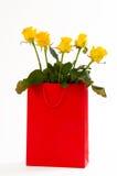 Bouquet de roses jaunes dans un sac de papier rouge, d'isolement sur le fond blanc Image libre de droits