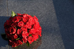 Bouquet de roses rouges sur la tombe Photos stock