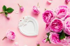Bouquet de roses de thé de rose de vue supérieure et cadre blanc de photo de vintage dans la forme du coeur sur le fond rose Cade Photos stock