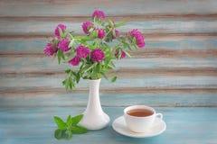 Bouquet de thé de trèfle violet dans une tasse et une menthe Images libres de droits