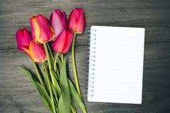 Bouquet de tulipe et carnet vide Image stock