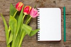Bouquet de tulipe et carnet vide Images stock