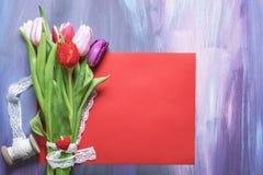 Bouquet de tulipes avec la dentelle sur une feuille de papier rouge Photo libre de droits