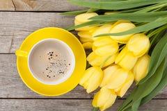 Bouquet de tulipes et tasse de café jaunes frais Photographie stock