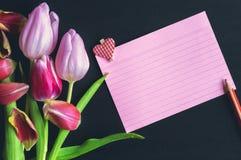 Bouquet de tulipes et une note de papier rayé Photos libres de droits